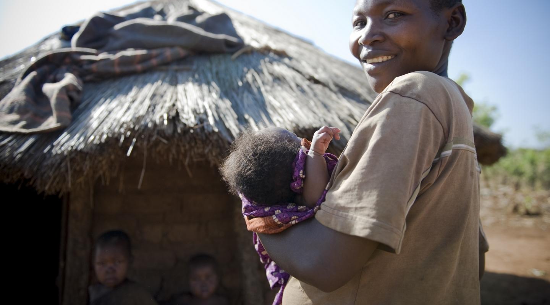 Nord Uganda. Donna con bambino davanti alla capanna di un villaggio. Ph Emanuela Colombo