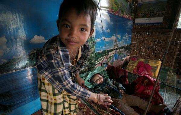 Un bimbo si prende cura del suo fratellino in Myanmar. Foto di Gianfranco Ferraro.