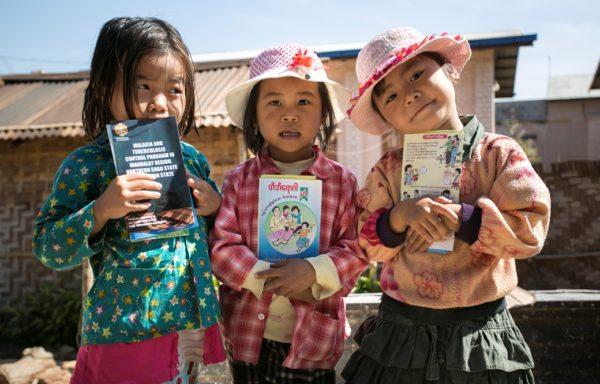 Bimbe tengono in mano volantini di sensibilizzazione sulla malaria in Myanmar. Foto di Gianfranco Ferraro.