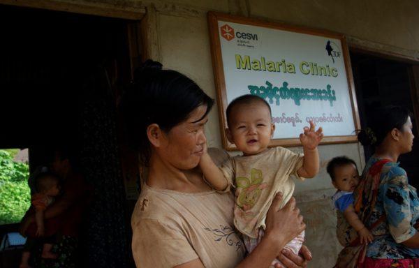 Una mamma con il suo bimbo fuori da una clinica per la malaria di Cesvi in Myanmar. Foto di Valeria Turrisi.