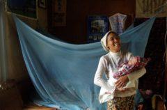 Una mamma e il suo bambino vicino al loro letto protetto dalla zanzariera come prevenzione della malaria. Foto di Valeria Turrisi.