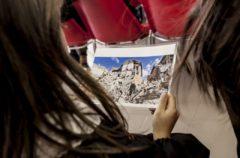 Due bambine guardano foto di case crollate a causa del terremoto. Foto di Roger Lo Guarro.