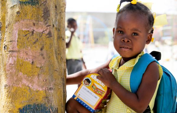 Haiti, una bimba con la sua merenda e il suo zainetto nel cortile della Casa del Sorriso