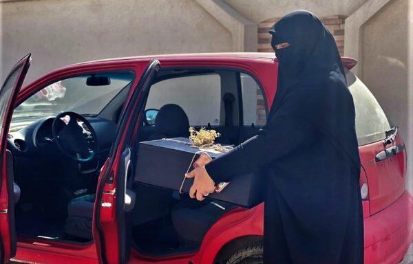 Malika con la sua automobile a noleggio che usa per la sua attività di pasticceria e delivery a domicilio.